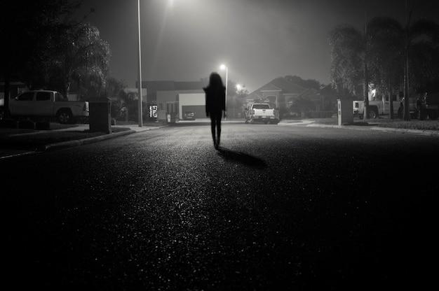 Ragazza che cammina in una strada urbana di notte sotto i riflettori