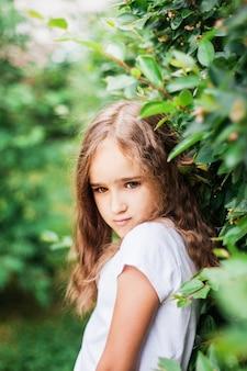 Ragazza che cammina nel giardino, piante verdi, arbusti, ritratto, verde, alberi, estate e primavera, bellezza, pantaloncini e maglietta, vacanze da scuola