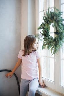 Ragazza che carteggia vicino alla finestra che aspetta santa claus, corona di natale sulla finestra, nuovo anno