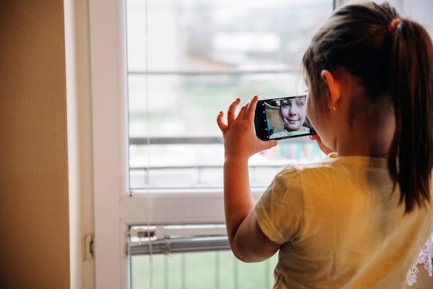 Ragazza che cattura selfie vicino alla finestra