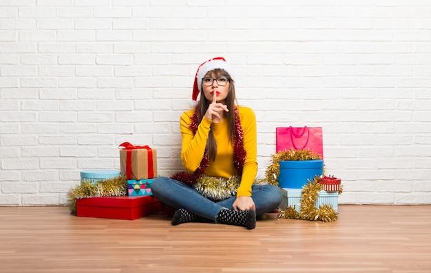 Ragazza che celebra le feste di natale mostrando un segno di chiusura bocca e gesto di silenzio