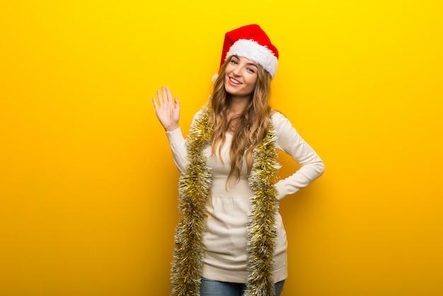 Ragazza che celebra le feste di natale su sfondo giallo