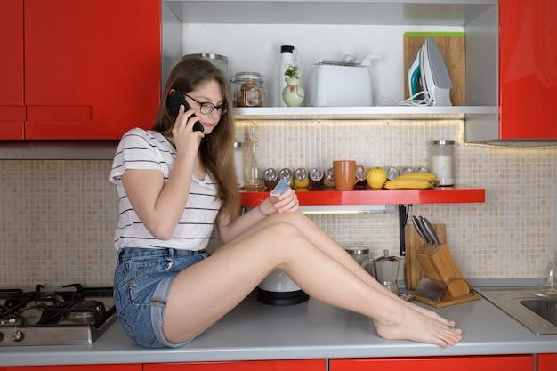 Ragazza che comunica sul telefono che tiene una carta di credito che si siede sopra il tavolo della cucina