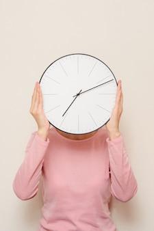 Ragazza che copre il viso da un orologio. la donna si nasconde dal concetto di stress e scadenza