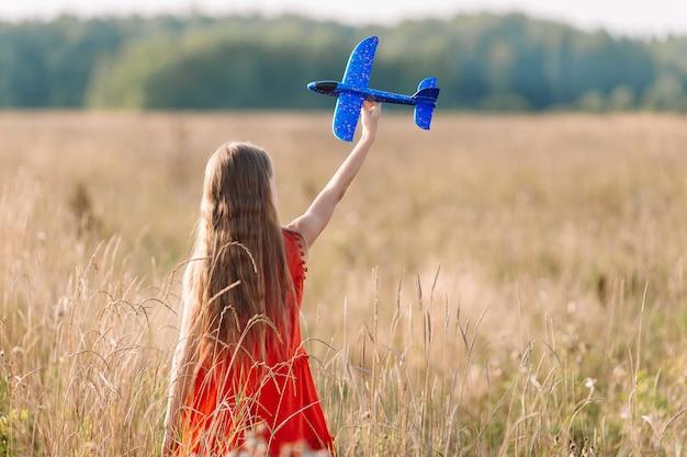 Ragazza che corre veloce e che tiene il giocattolo dell'aeroplano