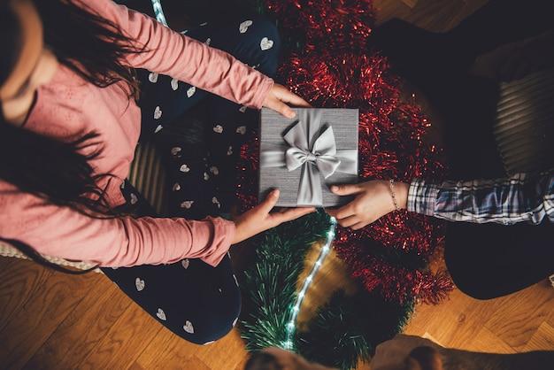 Ragazza che dà ad amico regalo di natale
