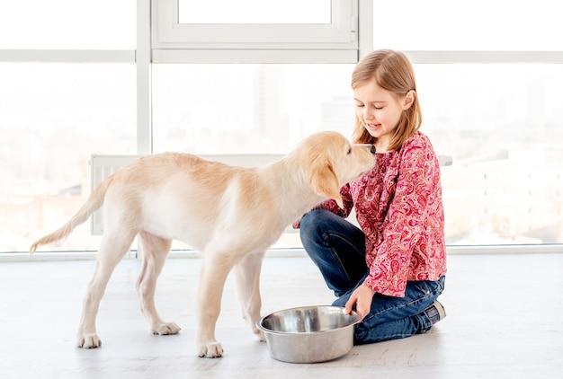 Ragazza che dà cibo al cane