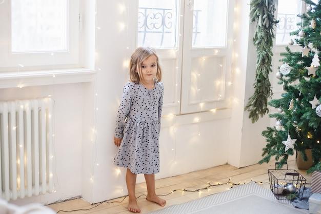 Ragazza che decora la casa con albero di natale e decorazioni natalizie.