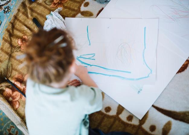 Ragazza che dipinge su carta e seduta sul pavimento