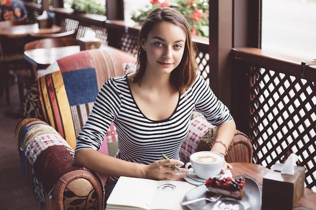 Ragazza che disegna una tazza di caffè nel taccuino