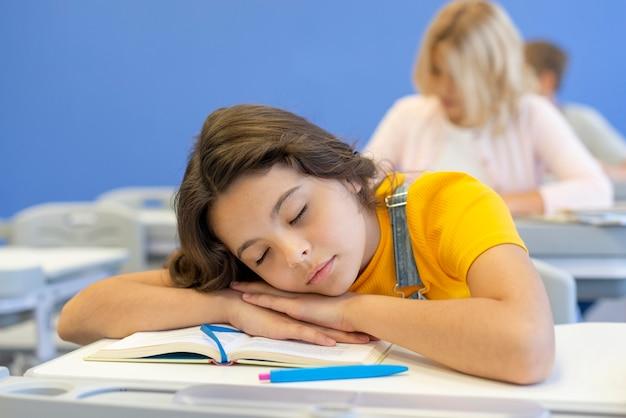 Ragazza che dorme in classe