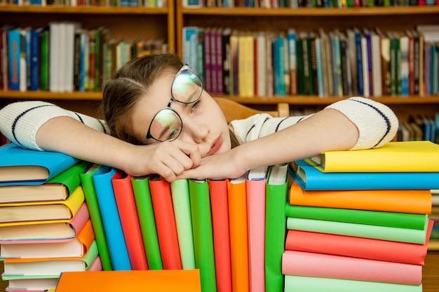 Ragazza che dorme sui libri in biblioteca