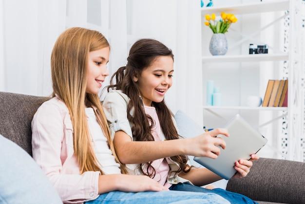 Ragazza che esamina il suo amico che gioca video gioco sulla compressa digitale a casa