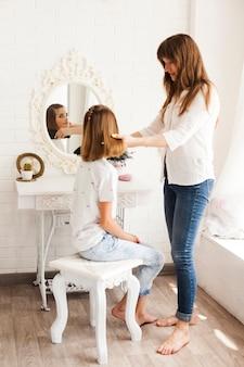 Ragazza che esamina specchio mentre madre che lega i suoi capelli a casa
