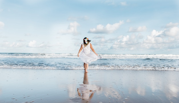 Ragazza che esce dal mare indossando abiti bianchi