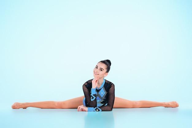 Ragazza che fa ginnastica danza sul blu