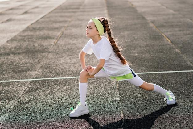 Ragazza che fa jogging in una soleggiata sera estiva, sdraiata sul tapis roulant, stadio, allenamento fisico, torna a scuola, stanca.