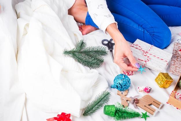 Ragazza che fa le cartoline di natale e le decorazioni per la famiglia e l'albero di natale. celebrazioni, festa di compleanno, regali,