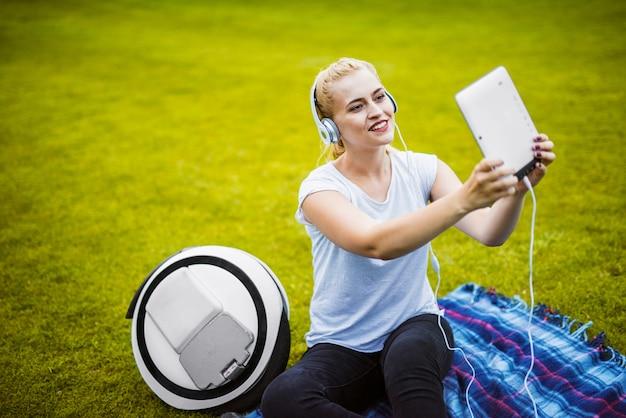 Ragazza che fa selfie sulla compressa che si siede sull'erba in parco.