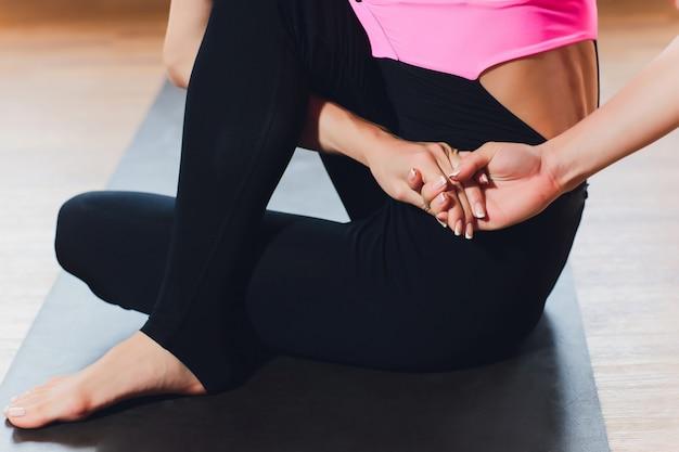 Ragazza che fa un asana chinandosi in avanti con le mani verso le gambe. seduto sul pavimento su una stuoia di yoga rosa. aderenza sui piedi. punti marma.