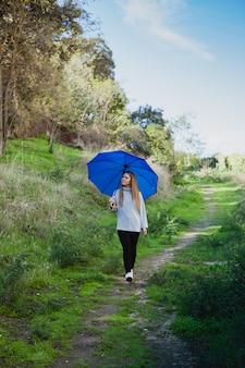 Ragazza che fa una passeggiata con un ombrello blu