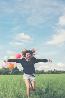 Ragazza che funziona con palloncini colores nel campo