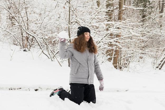 Ragazza che getta la palla di neve nella foresta di inverno