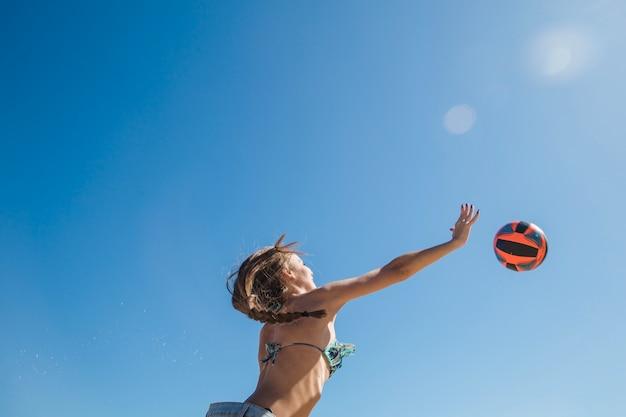 Ragazza che gioca a beach volley vista dal basso