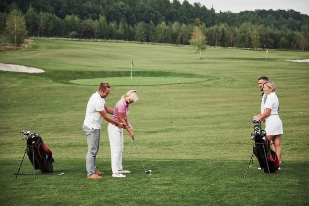 Ragazza che gioca a golf e che colpisce dal putter su verde. la sua insegnante aiuta a esplorare la tecnica e a fare i suoi primi colpi