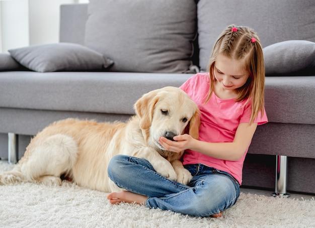 Ragazza che gioca con il cane a casa
