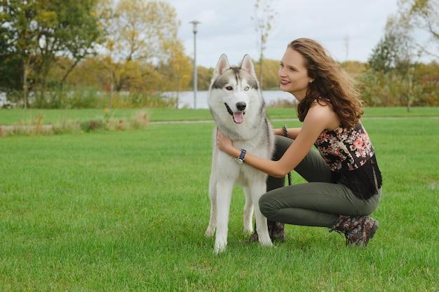 Ragazza che gioca con il cane husky nel parco cittadino. addestrare il cane.