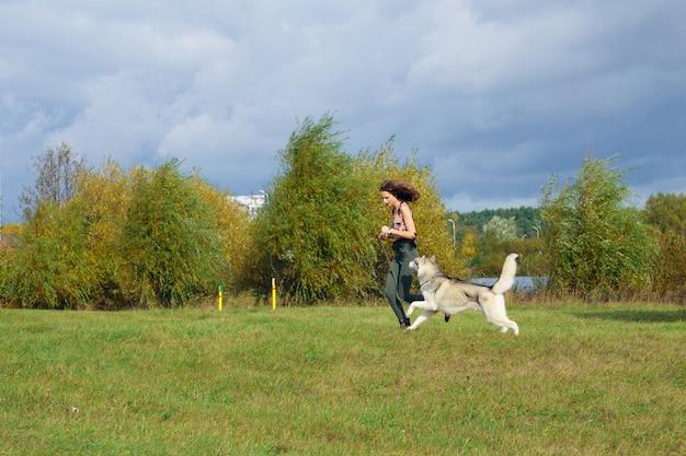 Ragazza che gioca con il cane husky nel parco cittadino. fare jogging con il cane.