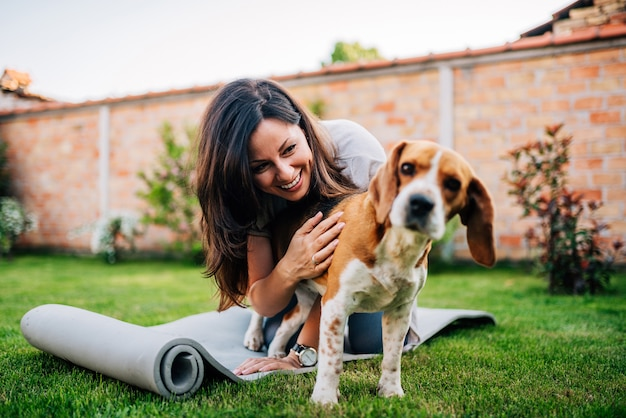 Ragazza che gioca con il suo cane beagle nel cortile.