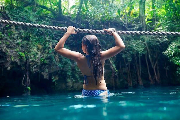 Ragazza che gioca con la corda nel sinkhole di cenote