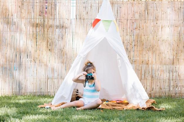 Ragazza che gioca con la macchina fotografica giocattolo in tenda