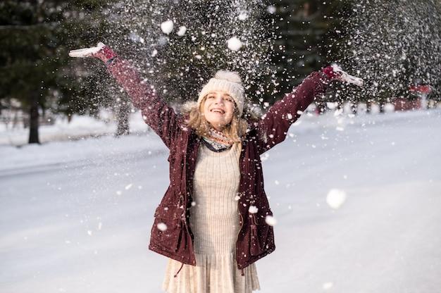 Ragazza che gioca con la neve nel parco. ritratto della ragazza felice che indossa abiti invernali innevati