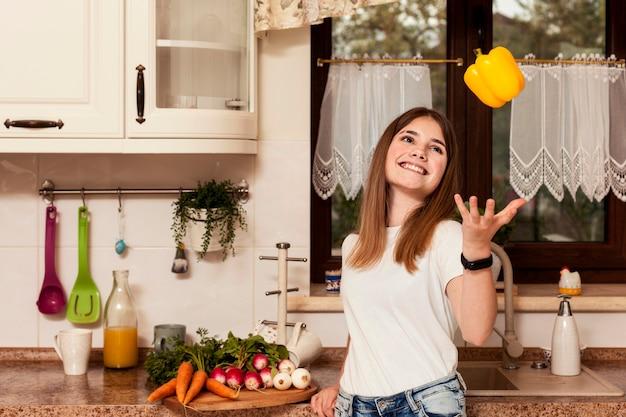 Ragazza che gioca con la verdura in cucina prima di cena