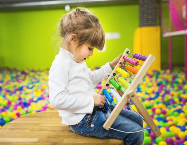 Ragazza che gioca con un giocattolo di legno dell'abaco