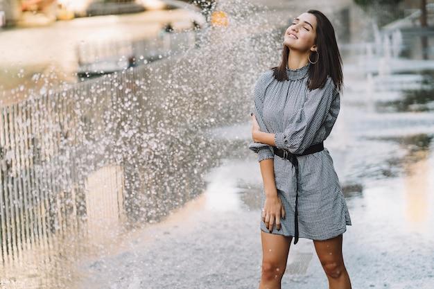 Ragazza che gioca e balla in giro su una strada bagnata