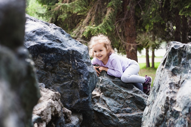Ragazza che gioca su rocce, arrampicata, infanzia e gioia, giocando con altri bambini, sviluppo