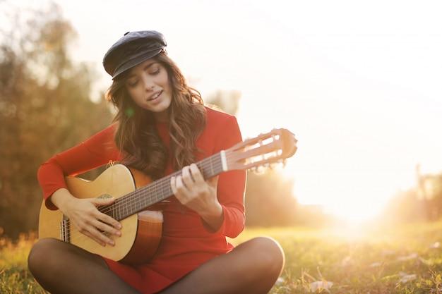 Ragazza che gioca su una chitarra nel parco