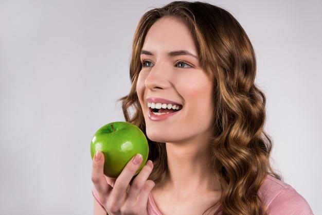 Ragazza che giudica sorridere verde della mela isolato.
