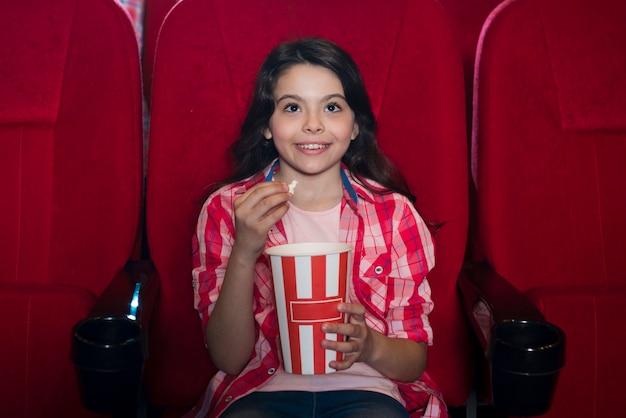 Ragazza che guarda film nel cinema