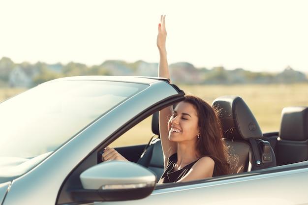 Ragazza che guida l'automobile di cabrio, sulla luce del tramonto