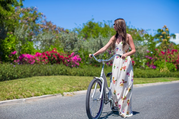 Ragazza che guida una bici sulla località di soggiorno tropicale