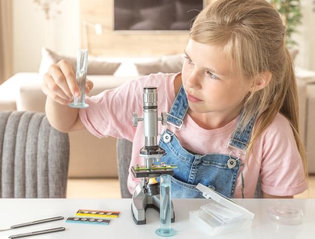 Ragazza che impara chimica che gioca con il microscopio a casa
