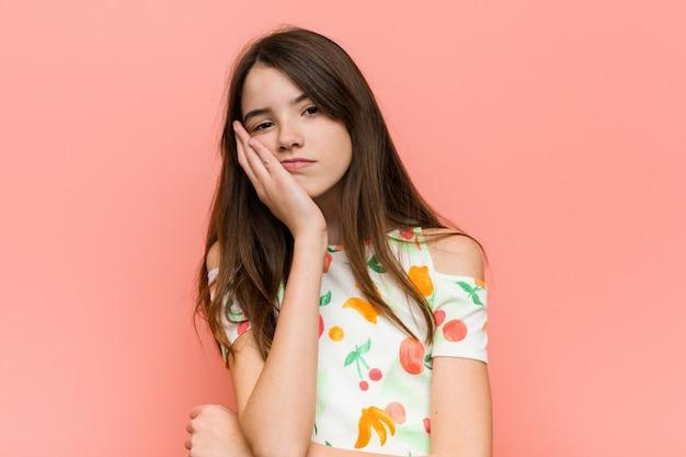 Ragazza che indossa abiti estivi contro un muro rosa che è bopink, affaticato e ha bisogno di una giornata di relax