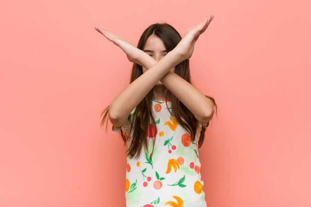 Ragazza che indossa abiti estivi contro un muro rosso mantenendo due braccia incrociate, rifiuto.