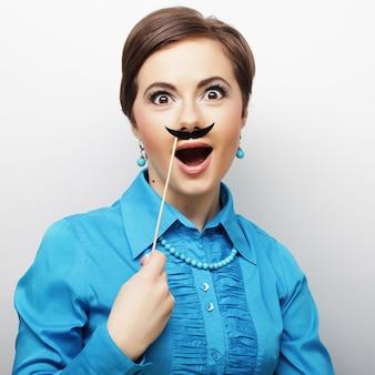 Ragazza che indossa baffi finti.