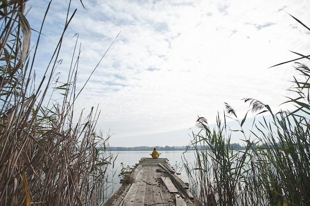 Ragazza che indossa giacca gialla brillante seduto sul vecchio molo e meditando nella posizione del loto sullo sfondo del bellissimo lago.